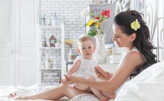 mamma som leker med en årig dotter på sängen foto