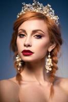 vacker ingefära kvinna med krona och röda läppar foto