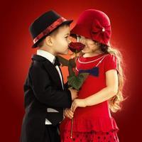 härlig liten pojke som ger en ros till flickan foto
