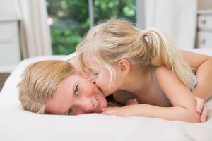 söt liten flicka och mamma på sängen foto