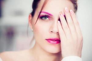 kvinnan med ett ljust rosa smink.