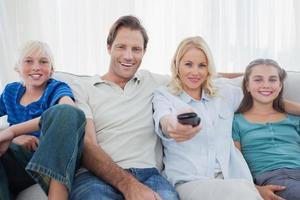 föräldrar som poserar med barn och tittar på tv foto