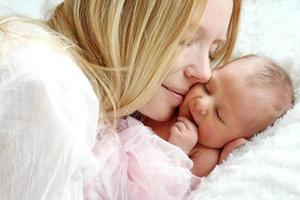glad mamma som snuggling nyfött barn i sängen foto