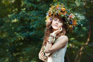 vacker flicka med krans på huvudet av fältblommor. foto