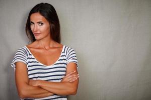 säker kvinna som står med korsade armar foto