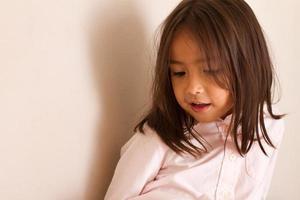 porträtt av lugn, seriös och säker liten flicka som tittar på foto