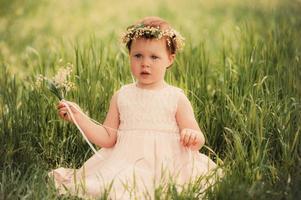 vacker liten flicka i krans av blommor