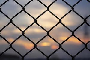 solnedgång genom ett staket foto