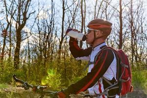 cyklist dricksvatten på cykel foto
