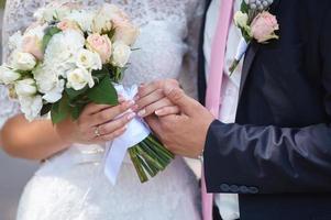 brudgummen håller sin bruds hand foto
