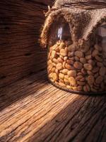 kaffebönor i burkar i solen foto