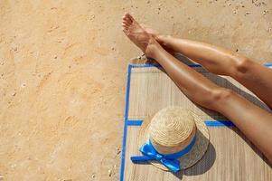 kvinnliga fötter och en stråhatt på stranden foto