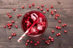 mogna granatäpplen med juice på träbakgrund foto