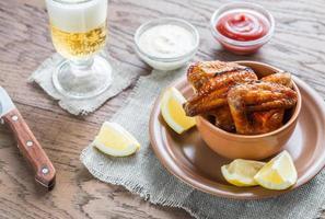 karamelliserade kycklingvingar med ett glas öl foto