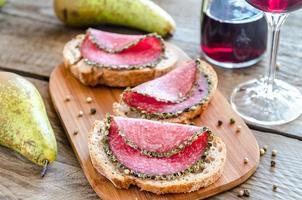 smörgåsar med italiensk salami med päron och vin foto