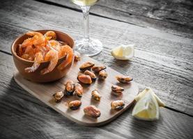 stekt räkor och musslor med ett glas vitt vin foto