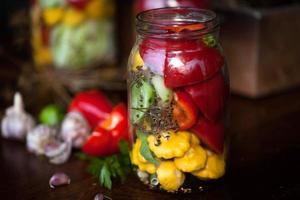 konserverade gurkor, paprika och patisson i burkar foto