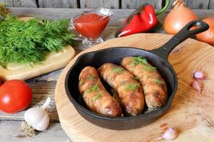 grillade köttkorvar i en stekpanna foto
