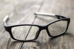 optiska glas på träbakgrund foto