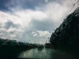regndroppar på vindrutan när du kör snabbt genom motorvägen. foto
