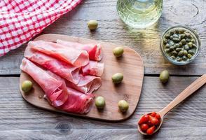jamon med kapris och oliver på träplattan foto