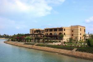 lyxiga strandhus i sjön med blå himmel foto