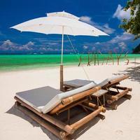 solstolar och paraply på exotiska tropiska vita sandstränder foto