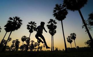 resenärer hoppar på palmträdets bakgrund av soluppgången foto