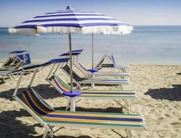solstolar och parasoller på stranden foto