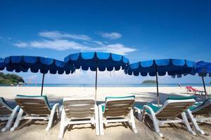 stolar och paraply på en vacker tropisk strand foto