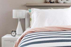 barns sovrum med vita kuddar och lampa på modern säng