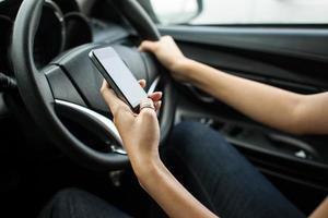 närbild av en kvinnahand som skickar en text under körning foto