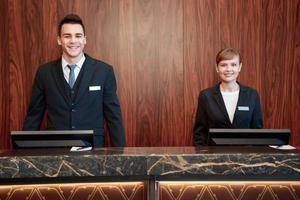 Hotellreceptionärer bakom disken foto