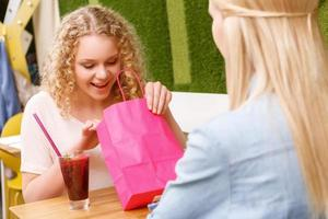flicka som tittar inuti påsen i caféet foto