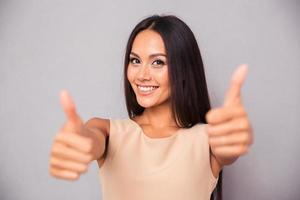 leende kvinna visar tummen upp foto