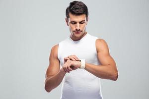 stilig fitness man använder smart klocka foto