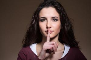 vacker flicka gör tystnad gest foto