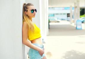 porträtt mode ung kvinna som bär solglasögon och t-shirt i foto
