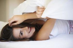 flirta av den naturliga flickan i sängen foto