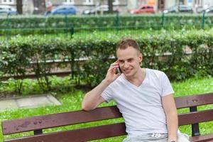 stående av den stiliga lyckliga mannen i parken som pratar i telefon. foto
