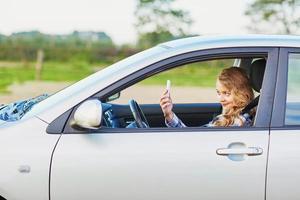 ung kvinna som kör en bil och använder telefon foto