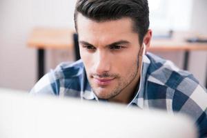 ung affärsman med hörlurar som använder pc foto