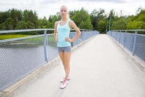 vacker och säker ung kvinnlig löpare står vid bron foto
