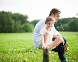 far och son sitter på stolpar i park foto
