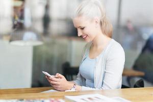 kvinna som använder mobiltelefonen på caféet foto