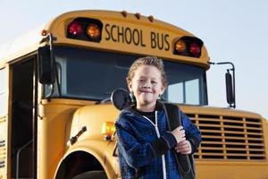 pojke framför skolbussen foto