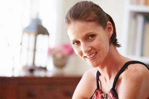 porträtt av en leende ung kvinna som sitter i ett rum foto