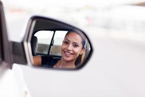 ung affärskvinnaförare tittar på sidospegeln foto