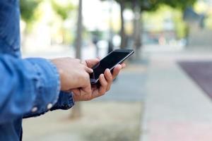 modern ung man med mobiltelefon på gatan.