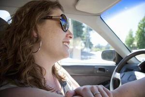 leende kvinna som kör bil foto